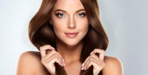 Kobieta trzymająca w dłoniach lśniące, piękne włosy